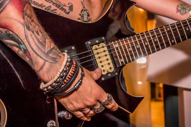 Detalhe de um menino tatuado tocando guitarra elétrica durante um cone de rocha.