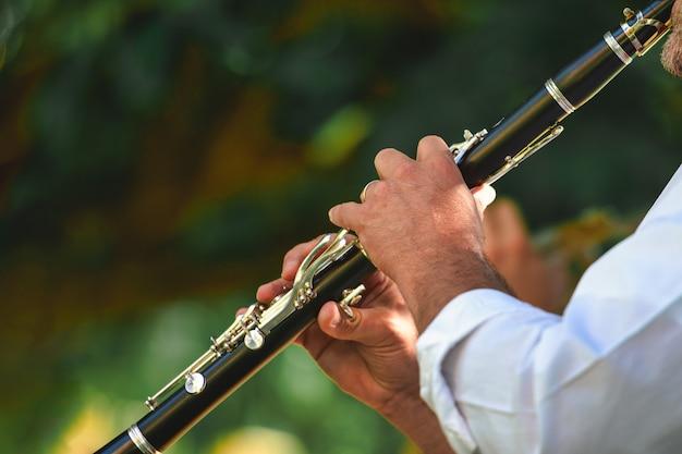 Detalhe de um músico de rua tocando clarinete