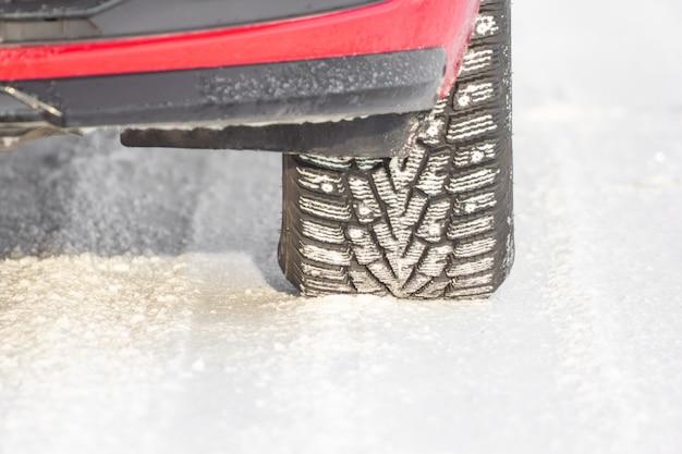 Detalhe de um pneu em uma estrada de inverno. conceito de condução de carro seguro.
