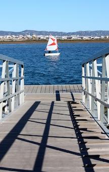 Detalhe de um ponto da ponte da passagem de ancoragem e no meio um barco de navigação pequeno.