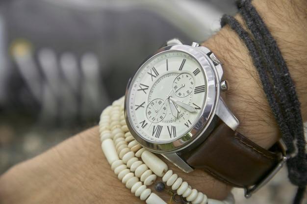 Detalhe de um relógio de pulso vintage usado por um menino com outras pulseiras, símbolo da passagem do tempo. um ótimo acessório para um look perfeito.