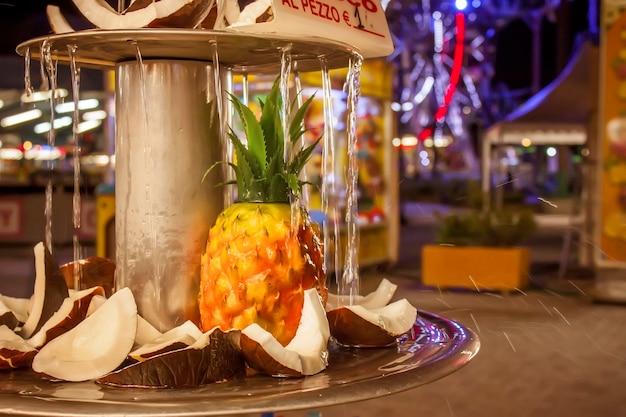 Detalhe de uma barraca de doloci em um parque de diversões italiano com rifrescati de coco e abacaxi por uma cachoeira fina.