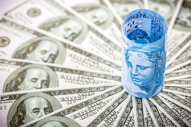 Detalhe de uma cédula de 100 reais com cédulas de 100 dólares