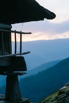 Detalhe de uma construção típica horreo da vila rural com vista para o vale da montanha com floresta ao nascer do sol