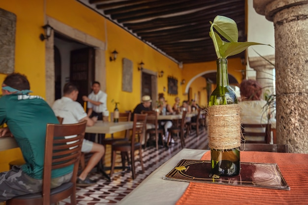 Detalhe de uma garrafa verde para uso ornamental colocada sobre a mesa de um restaurante em valladolid, méxico