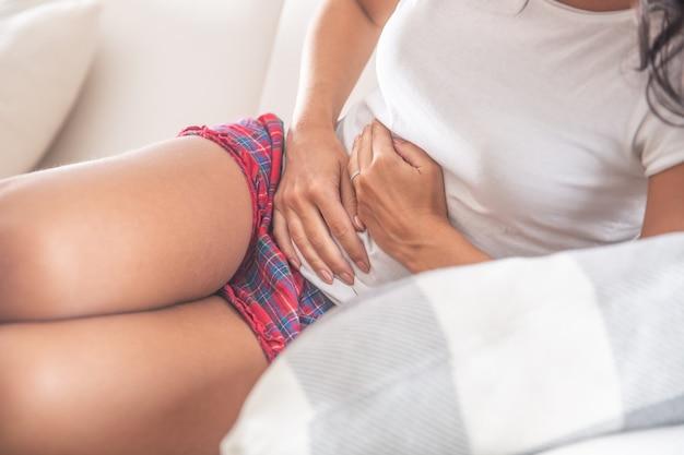 Detalhe de uma jovem mulher sentada no sofá, inclinando-se para o lado e segurando o estômago dolorido com as duas mãos.