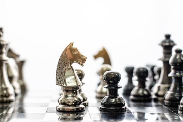 Detalhe de uma mão fazendo o primeiro movimento em um jogo de xadrez, movendo o peão um campo para a frente. foco seletivo