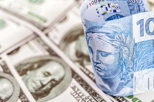 Detalhe de uma nota de cem reais do brasil, presa entre notas de 100 dólares americanos