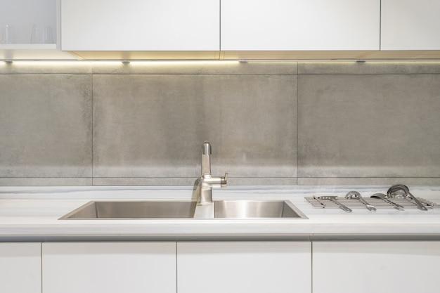 Detalhe de uma pia de cozinha retangular branca com torneira de água de cromo contra uma parede de azulejos