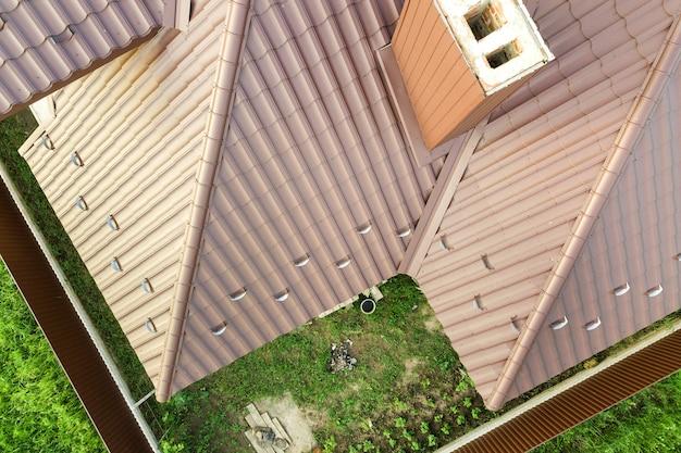 Detalhe de uma superfície de telhado de casa coberta com telhas de metal marrom.