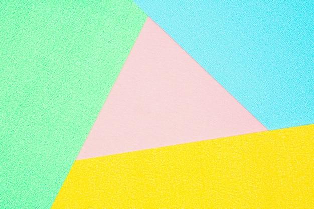Detalhe de uma textura de papel de cor verde, rosa, azul e amarelo.