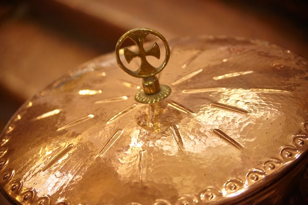 Detalhe de uma tigela de cobre com uma cruz acima usada como objeto litúrgico no rito