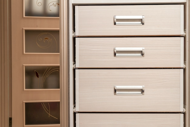Detalhe do baú do armário de móveis de madeira com frente de gavetas, alças de metal, estilo vintage