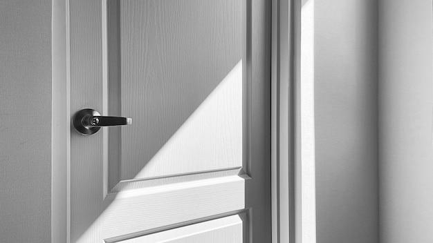 Detalhe do close up da porta branca com sombra, fundo preto e branco.