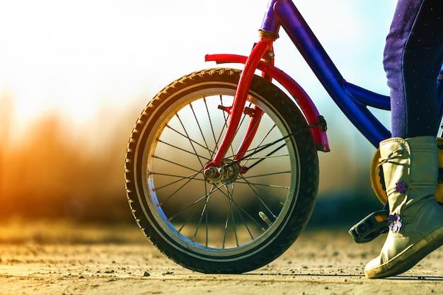 Detalhe do close-up de pés de criança menina em uma bicicleta de criança