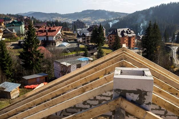 Detalhe do close-up de quadro de telhado de feixes de madeira serrada e de chaminé de madeira ásperos feitos de blocos da isolação da espuma no verde borrado. conceito de construção, cobertura, construção e renovação.