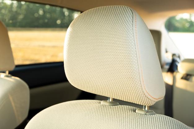 Detalhe do close up dos encostos de cabeça do carro bege claro.