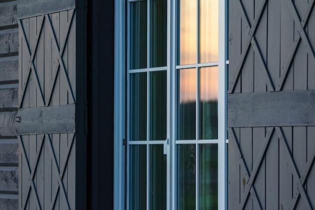 Detalhe do exterior da casa de madeira. reflexo da luz da noite quente nas janelas de vidro.
