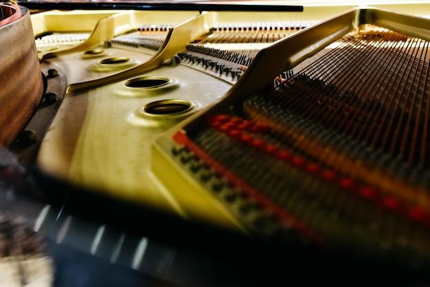 Detalhe do interior de um piano com o tampo, cordas e alfinetes.