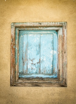 Detalhe do pequeno portão de madeira velho pintado de azul e fechado