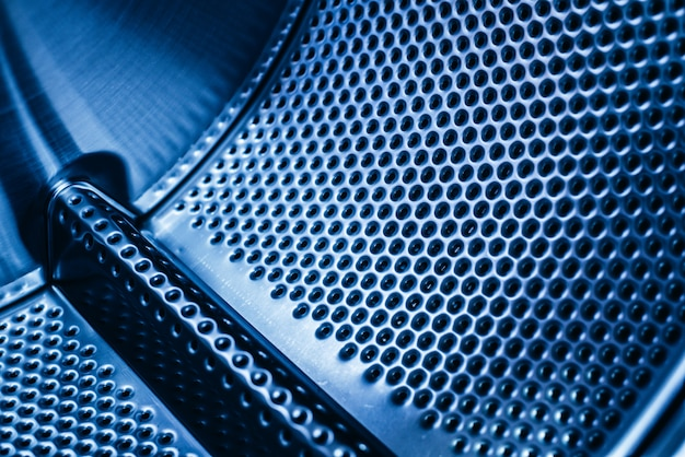 Detalhe do tambor de uma máquina de lavar, textura industrial de aço com furos.