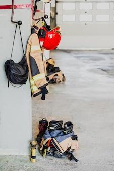 Detalhe do traje de trabalho de um bombeiro preparado para ação ao lado do material para extinguir incêndios com segurança.