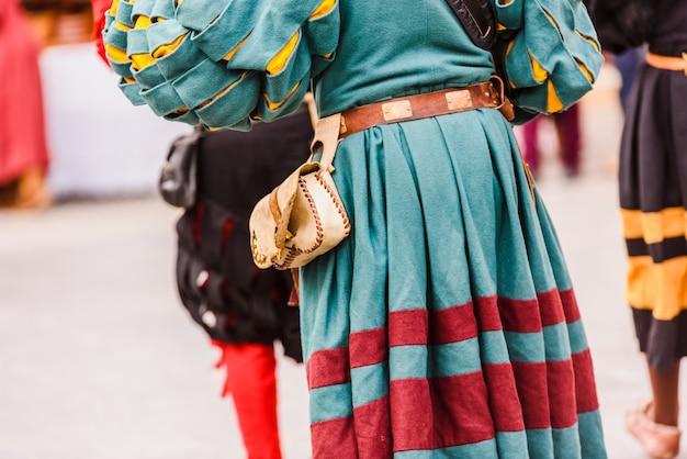 Detalhe dos trajes dos atores disfarçados com roupas medievais antigas durante um festival.