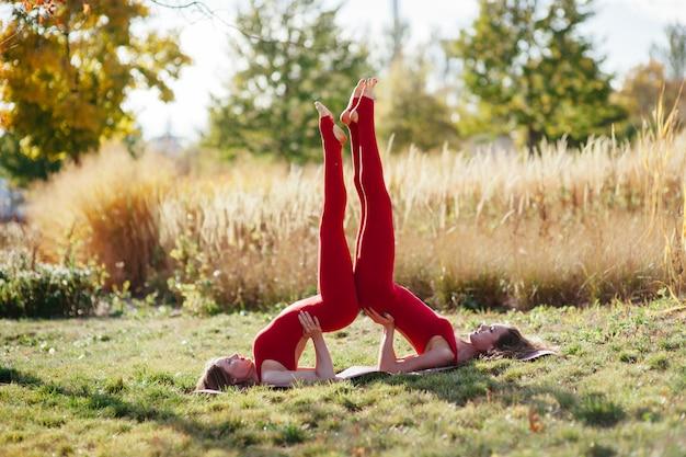 Detalhe horizontal de mulheres fazendo ioga ao ar livre ao pôr do sol com reflexo de lente.
