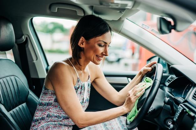 Detalhe interior do carro. mulher de meia-idade feliz limpa e limpa o interior do carro.