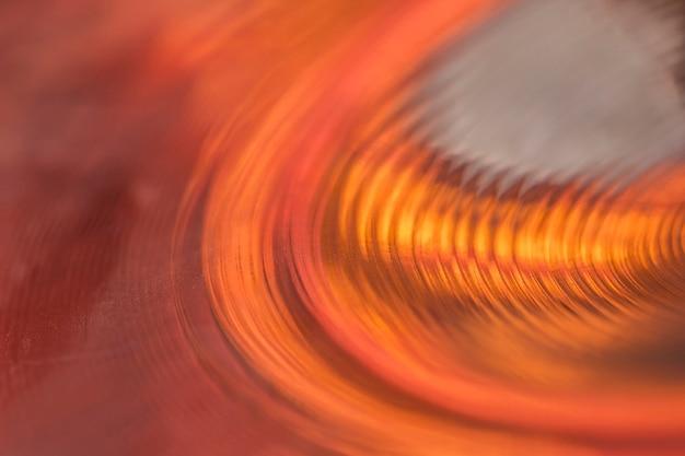 Detalhe macro dos círculos concêntricos de uma placa de bateria enquanto ela brilha no holofote