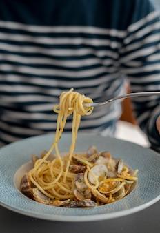 Detalhe masculino comendo macarrão espaguete com amêijoas e salmonete, comida mediterrânea