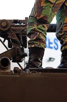 Detalhe montado da metralhadora e um pé e uma bota militares sobre um veículo.