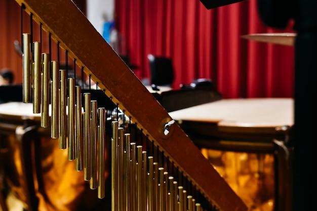 Detalhe musical de um windchimes dourado.