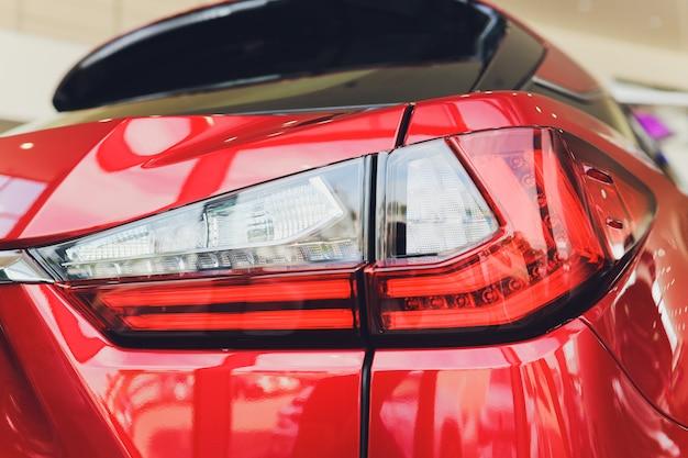 Detalhe na luz traseira de um carro vermelho.
