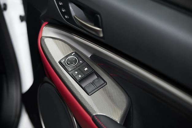 Detalhe nos botões que controlam as janelas no carro vermelho.