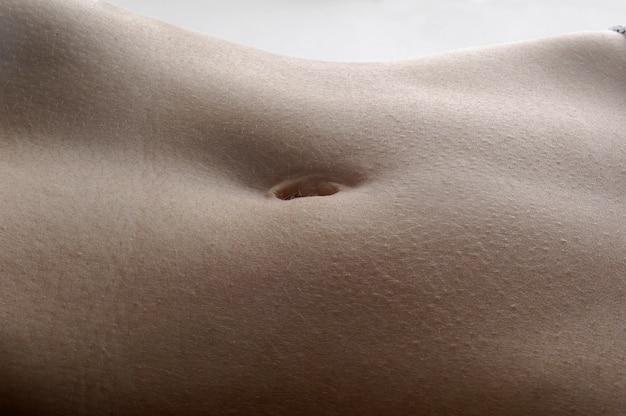 Detalhe o umbigo de uma mulher com fundo branco