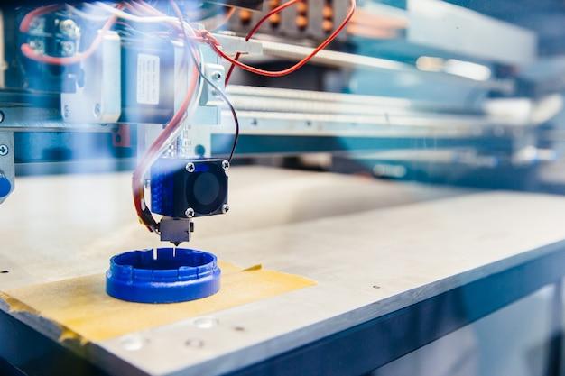 Detalhe plástico azul recém-impresso na plataforma da impressora 3d