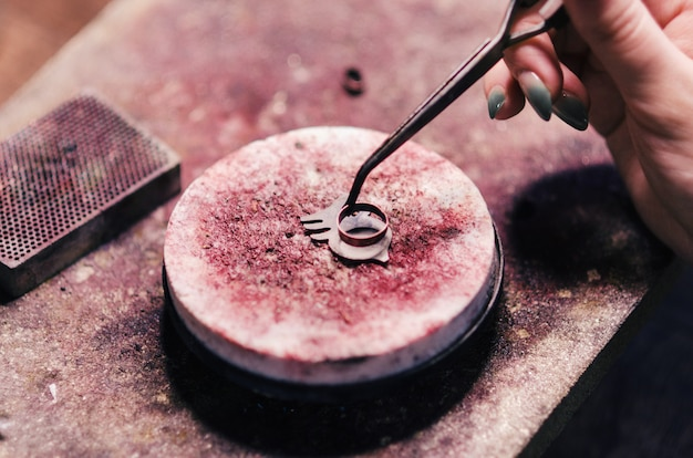 Detalhes ardentes da jóia em uma pedra com um queimador de gás. oficina de casa, feito à mão.