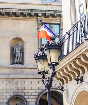 Detalhes arquitetônicos de fachadas de edifícios em paris com bandeira francesa