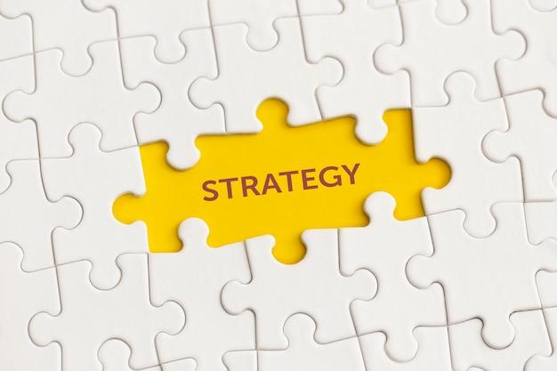 Detalhes brancos do quebra-cabeça com o texto estratégia em fundo amarelo