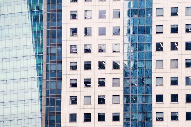 Detalhes da fachada de um arranha-céus moderno feito do close up de vidro e de aço.
