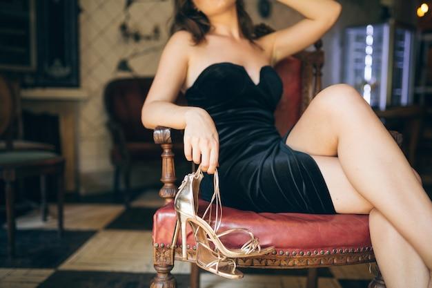 Detalhes da moda de mulher bonita e elegante sentada descalça em um café vintage em vestido de veludo preto, senhora rica e elegante, tendência elegante, tirou os sapatos, sandálias de salto alto douradas, calçados