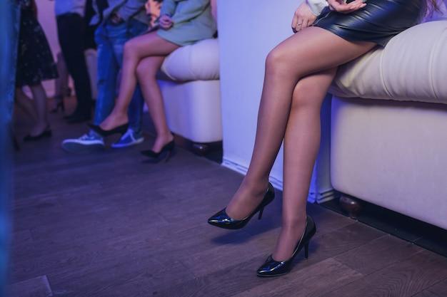 Detalhes da moda de mulher bonita e elegante sentada em um café vintage com vestido de veludo preto rico, elegante senhora elegante tendência pernas longas e magras usando sapatos de sandálias de salto alto