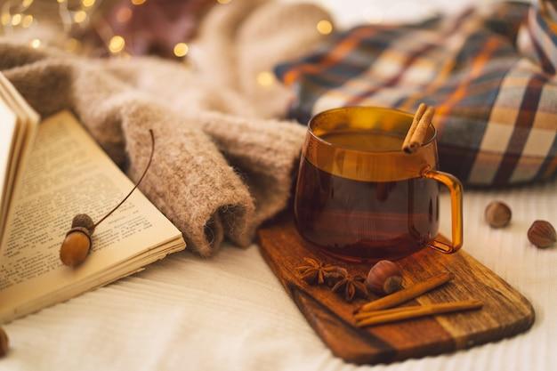 Detalhes da natureza morta em suéteres de interior de casa e xícara de chá com decoração de outono e livros para leitura