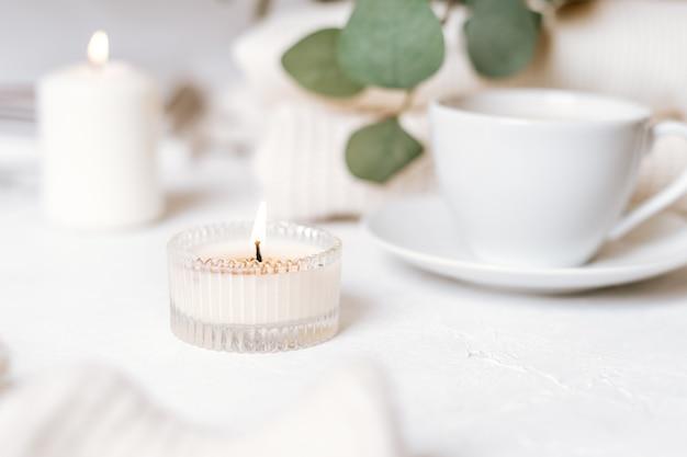 Detalhes da natureza morta no interior da casa da sala de estar. xícara de café, algodão, livro, vela, suéter. temperamental. conceito de inverno outono aconchegante em branco. decoração.