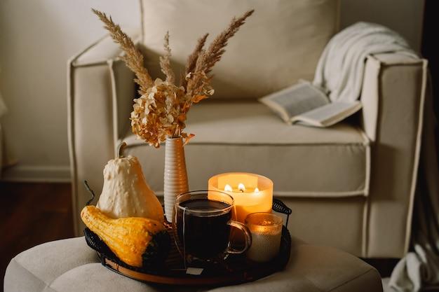 Detalhes da vida ainda no interior da casa da sala de estar. abóbora e chá com velas em uma bandeja de servir. descanso e leitura. outono aconchegante