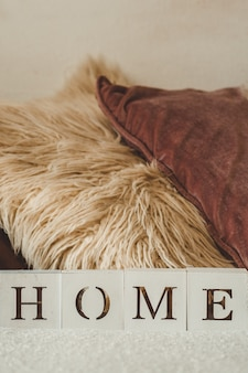 Detalhes da vida ainda no interior da sala de estar e a inscrição casa. muitas almofadas decorativas aconchegantes. descansar. conceito aconchegante de outono ou inverno, malhas. conceito de casa