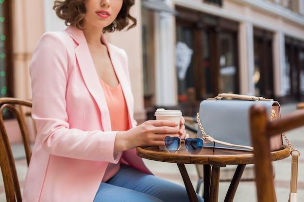 Detalhes de acessórios de uma mulher bonita com roupa elegante sentada no café, óculos de sol, bolsa, cores rosa e azul, tendência da moda primavera-verão, estilo elegante, clima romântico, férias na europa,