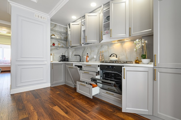 Detalhes de close da cozinha clássica contemporânea cinza e branca projetada em estilo moderno, todas as portas e gavetas de móveis estão abertas