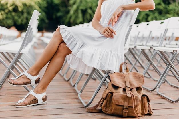 Detalhes de close-up de mulher vestida de branco sentada no teatro ao ar livre de verão na cadeira sozinha, tendência da moda de estilo de rua de primavera, acessórios, viajando com mochila, pernas magras em sandálias